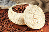 Coffee beans in wicker basket on wooden background — Stock Photo