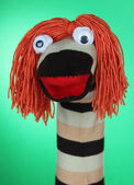 Cute sock puppet on green background — Photo