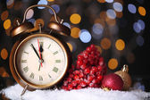 Alarm clock with snow and Christmas decorations on table on bright background — Stock Photo