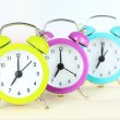 Colorful alarm clocks on table on light background — Stockfoto