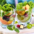 Fruit salad in glasses, on wooden table, on bright background — Stock fotografie