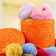 Multicolored clews in wicker basket with bright scarf closeup — Stock Photo