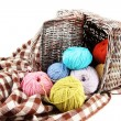 Multicolored clews in wicker basket with plaid closeup — Stock Photo #33476933