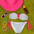 Swimsuit and beach items on green background — 图库照片