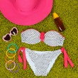 Swimsuit and beach items on green background — Stok fotoğraf