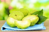 Osage Orange fruits (Maclura pomifera) in basket, on wooden table, on nature background — Stock Photo