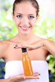 Beautiful girl with shower gel close-up on natural background — Stock Photo