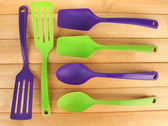 Plastic kitchen utensils on wooden background — Stock Photo