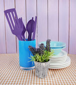 Plastic kitchen utensils in stand with clean dishes on tablecloth on wooden background — Stock Photo