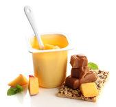 Smaczny jogurt z kawałkami owoców, ciastka i cukierki toffi na białym tle — Zdjęcie stockowe