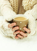 Female hands with hit drink, on light background — Stock Photo