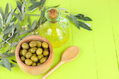 Olivolja gren och olivolja i skål på träbord — Stockfoto