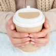 Hot drink in paper cup in hands with snow close up — Stock Photo