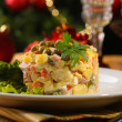 Russian traditional salad Olivier, on color napkin, on wooden table, on bright background — Stock Photo #33480875