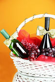 Gift basket with wine on orange background — Stock Photo