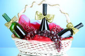 Gift basket with wine on blue background — Stock Photo