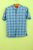 Male shirt on wooden hanger on wall background — Stock Photo
