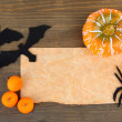 Old paper with Halloween decorations on grey wooden background — Stock Photo #33526291