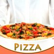 Waiter holding a dish with baked pizza on white background close-up — Stock Photo