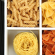 Different types of pasta in white wooden box sections close-up — Stock fotografie