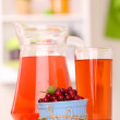 Pitcher and glass of cranberry juice with red cranberries on table  — Stock Photo