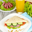 Stock Photo: Composition with fruit juice and tasty sandwich with salami sausage and vegetables on color napkin, on wooden table background