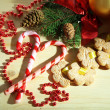 Cookies on ribbons with Christmas decorations on wooden table — Stock Photo #33664371