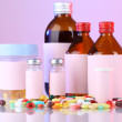 Pills and medicine bottles on pink background — Stock Photo