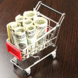 Stock Photo: Shopping trolley with dollars, on dark background