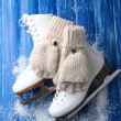 Wool fingerless gloves and skates for figure skating, on wooden background — Stock Photo