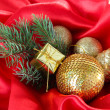 Beautiful Christmas decor on red satin cloth — Stock Photo #33664251