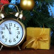 Alarm clock with Christmas tree and present on table on blue background — Stock Photo