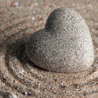 Grey zen stone in shape of heart, on sand background — Zdjęcie stockowe