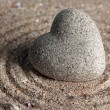 Grey zen stone in shape of heart, on sand background — Zdjęcie stockowe #33665687