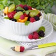 Fruit salad in bowl, on wooden table, on bright background — Stock fotografie