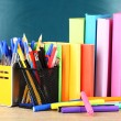 Stock Photo: Office supplies on table on school board background