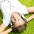 Young man relaxing on carpet and listening to music — Stock Photo
