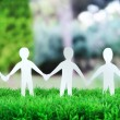 Paper people in social network concept on green grass outdoors — Stock fotografie