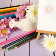 Composition of flowers and  small easel with picture on wooden table close-up — Stock Photo
