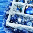 Christmas toys in wooden box on blue background — Stock Photo