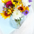 Bouquet of wild flowers in glass vase on light background — Stock Photo
