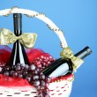 Gift basket with wine on blue background — Stock Photo #33669669