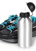Sports bottle and sneakers isolated on white — Stock Photo