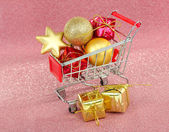Christmas gifts in shopping trolley, on pink shiny background — Stock Photo