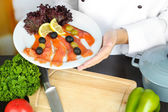 Cook hands holding dish at workplace — Stock Photo
