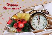 Alarm clock with Christmas decoration on golden cloth background — ストック写真