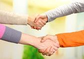 Handshakes on bright background — Stock Photo