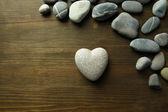 Šedý kámen ve tvaru srdce, na dřevěné pozadí — Stock fotografie