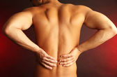 Young man with back pain on dark background — Stock Photo