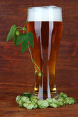 Glass of beer and hops, on wooden table — Stock Photo